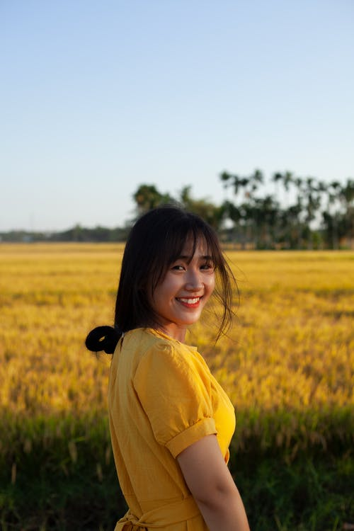 Woman in Yellow Dress Standing on Green Grass Field