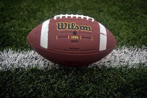 Brown Football on Green Grass