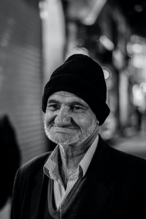 Man in Black Knit Cap and Black Suit Jacket in Grayscale Photography