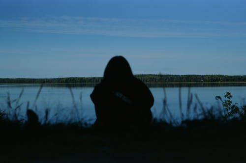Person Sitting Near Lake