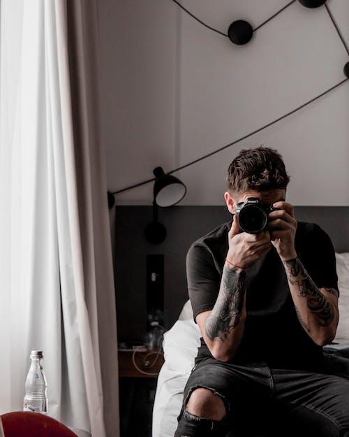 Man in White Crew Neck T-shirt Holding Black Camera