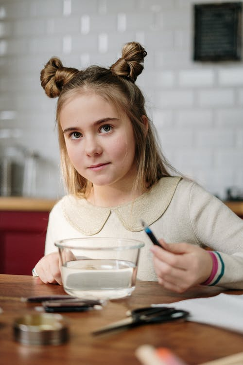 Girl With Cute Hairstyle Holding Dye Near Bowl with Water