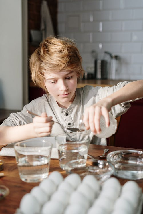 Boy in Grey Shirt Holding Clear Glass Pouring Liquid on Spoon