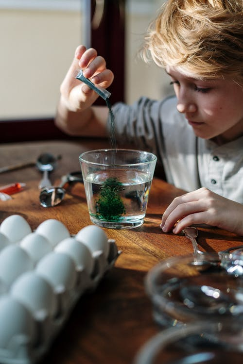 Boy Pouring Green Color Powder on Glass of Water