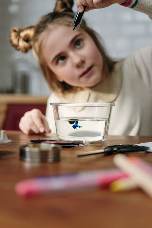 Girl Dropping Blue Dye on Bowl with Water
