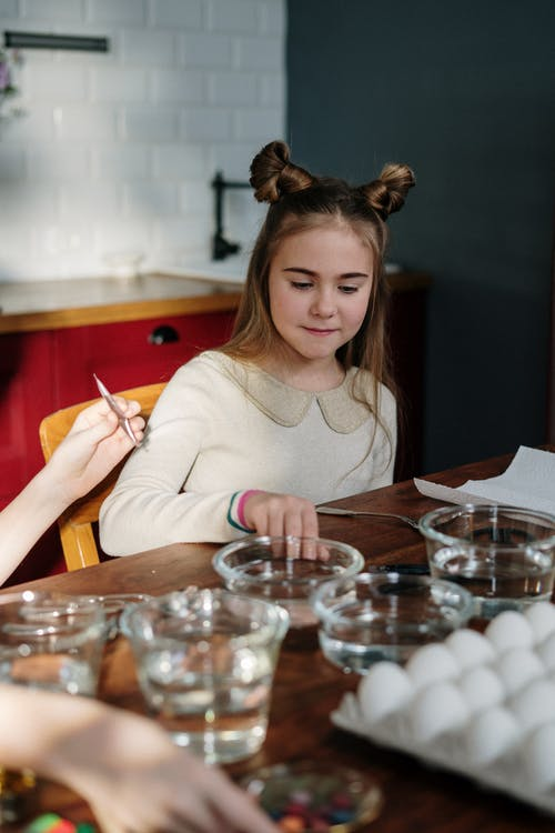 Girl with Cute Hairstyle Making Easter Eggs