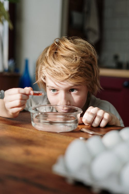 Boy Squeezing Orange Dye on Bowl with Water