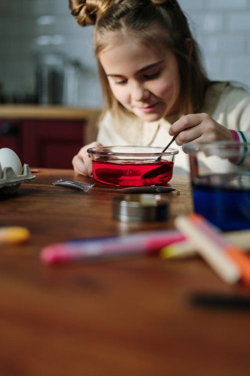 Girl Mixing Red Dye on Bowl of Water