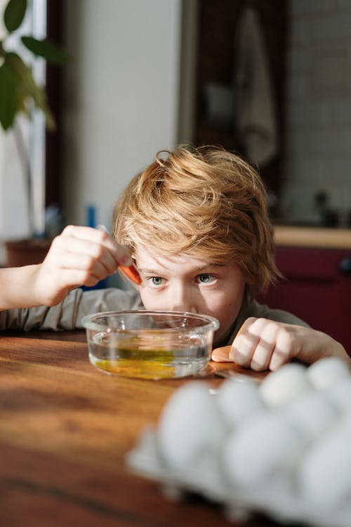 Blonde Haired Boy Squeezing Orange Dye on Bowl with Water