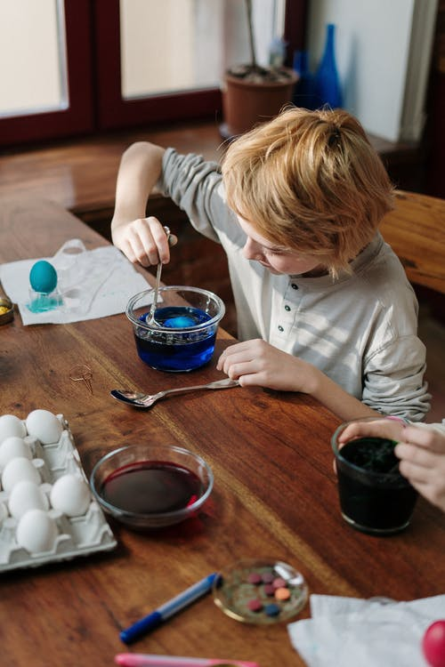 Boy Dipping Egg in Blue Water