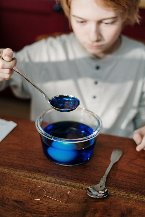 Boy Holding Silver Spoon with Blue Liquid
