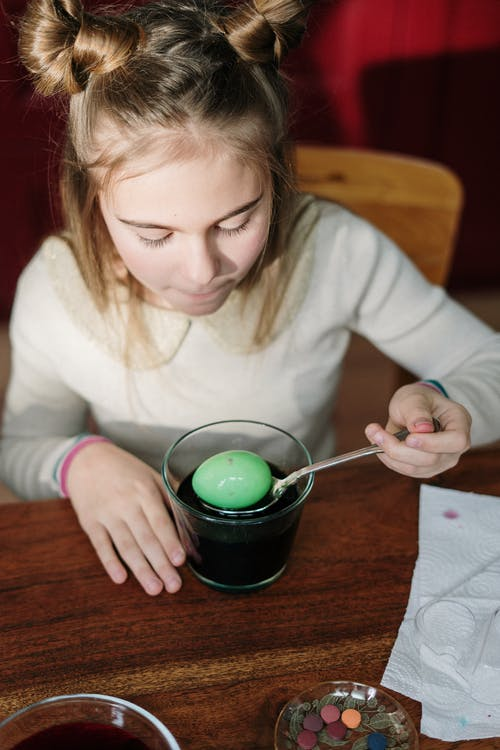 Girl in White Sweater Holding Silver Spoon Scooping Green Egg