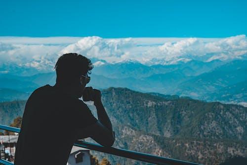 Mężczyzna W Czarnej Koszuli Stojący Na Szczycie Góry Picia Kawy