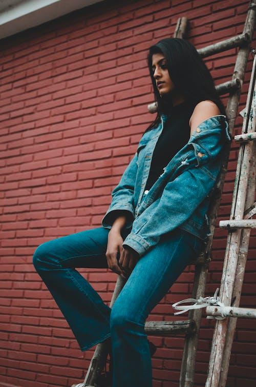Woman in Blue Denim Jacket and Blue Denim Jeans Sitting on Wooden Ladder