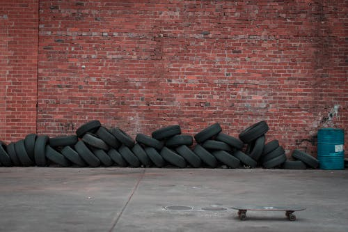 Black Car Tires Against Brown Brick Wall