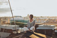 Woman In White Sweater Sitting On A Roof