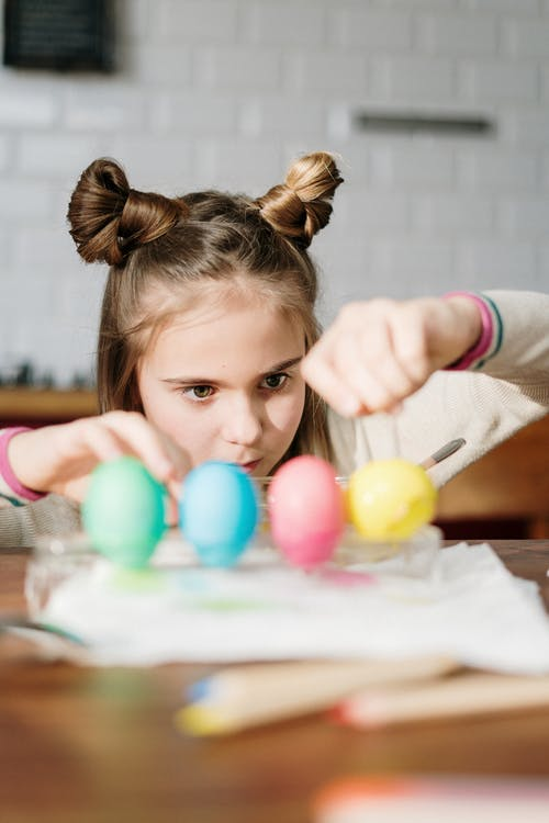 Girl with Cute Hair Buns Making Colorful Easter Eggs