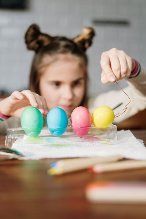 Person Holding Four Colored Eggs