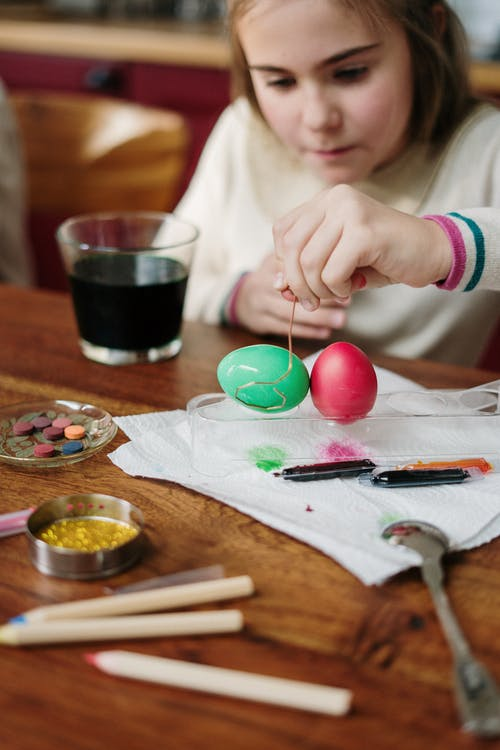 Girl in White Long Sleeve Sweater Holding Colored  Egg