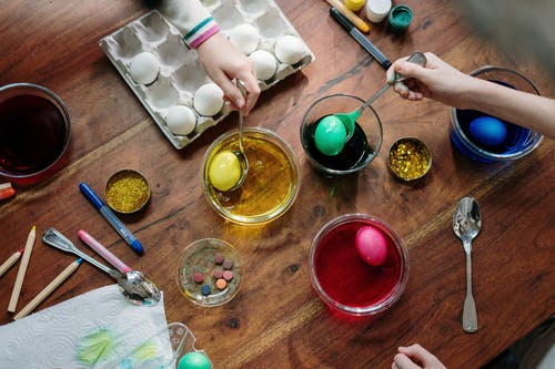 People  Holding  Silver Spoons With Colored Eggs