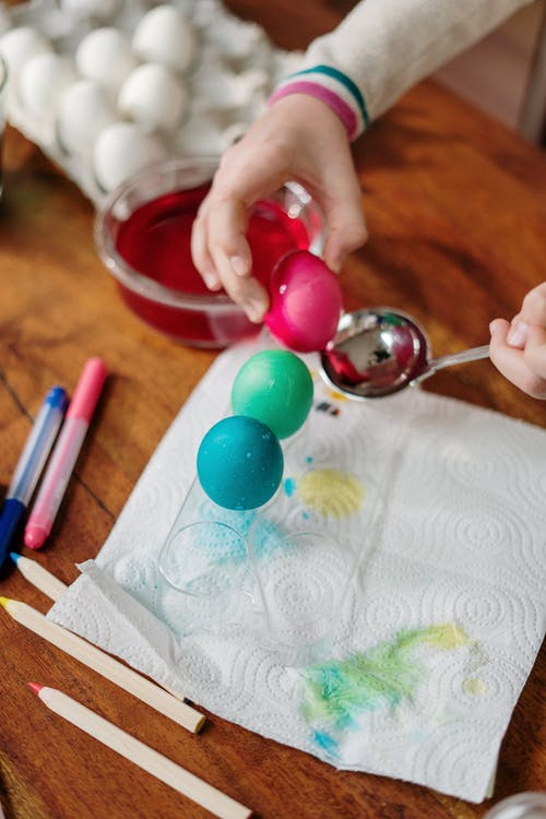 Person Holding Colored Egg and  Silver Spoon