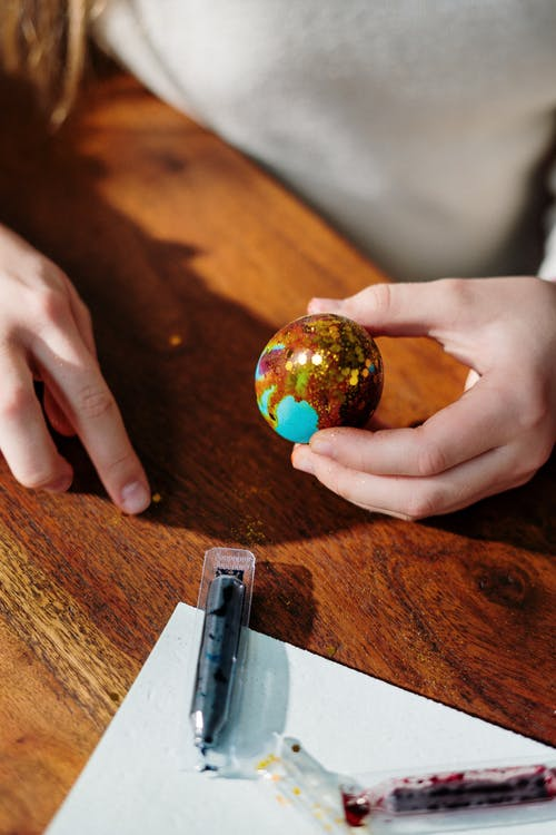 Person Holding Blue and Brown Egg