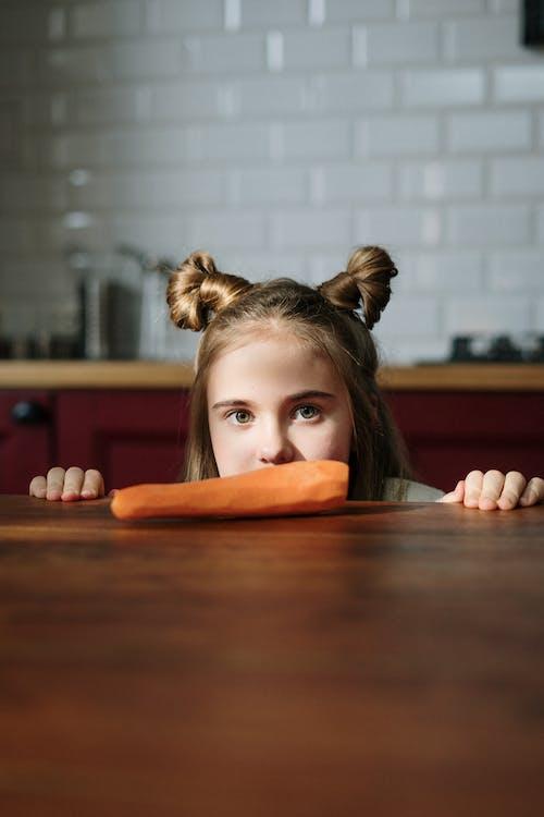 Girl Peeking Over Brown Wooden Table