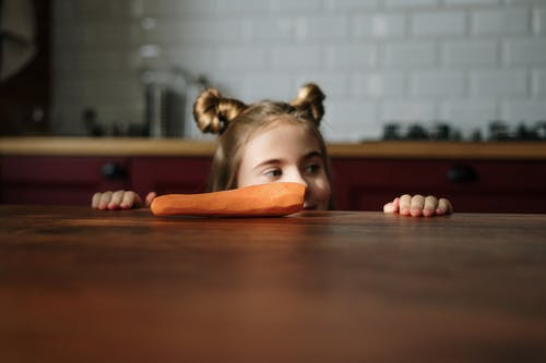 Girl Peeking Over Brown Wooden Table