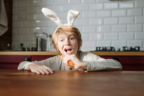 Boy with Bunny Ears Eating Carrot