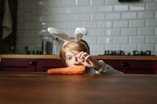 Boy Grabbing Carrot on the Table