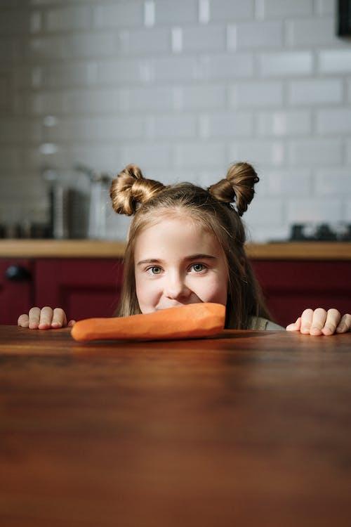 Girl Peeking Over Wooden Table