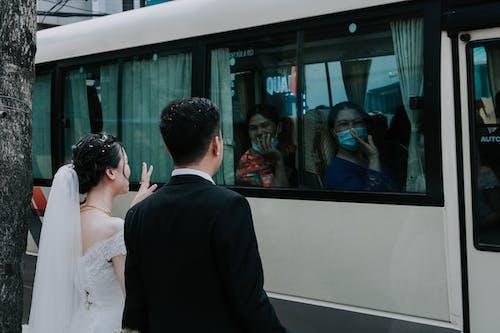 Man in Black Suit Standing Beside Woman in White Wedding Dress Waving Goodbye