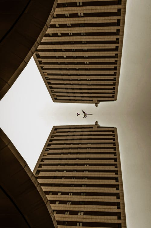 Low Angle Photography of Airplane Flying over Brown Concrete Building