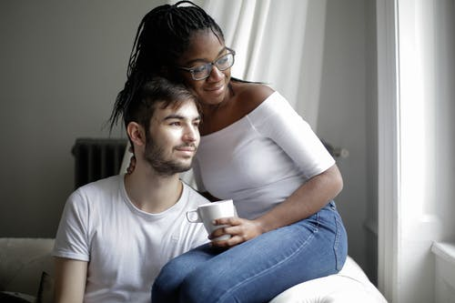Cheerful multiethnic couple resting on sofa and looking through window at home