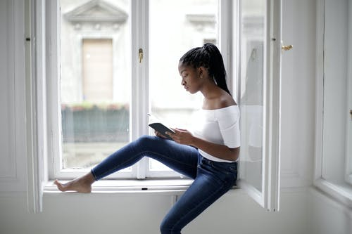 Woman in White Tank Top and Blue Denim Jeans Sitting on Windowsill