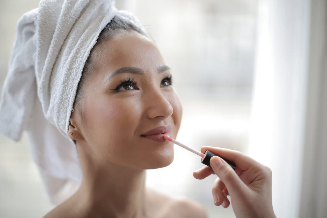 Beautiful young ethnic lady applying makeup on lips after shower at home