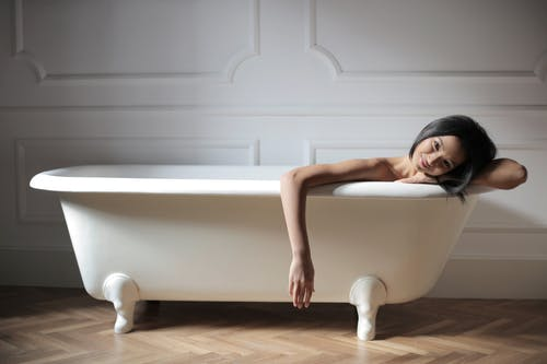 Cheerful young ethnic lady relaxing in bath in modern bathroom
