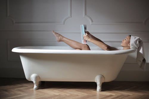 Person in Bathtub Reading Magazine