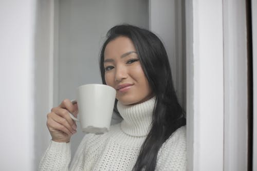 Positive young Asian lady drinking coffee while standing near window in modern apartment