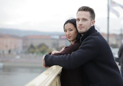 Positive young multiracial couple hugging on bridge on street in city