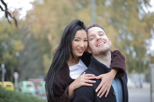 Cheerful multiethnic young couple hugging while walking on street in park