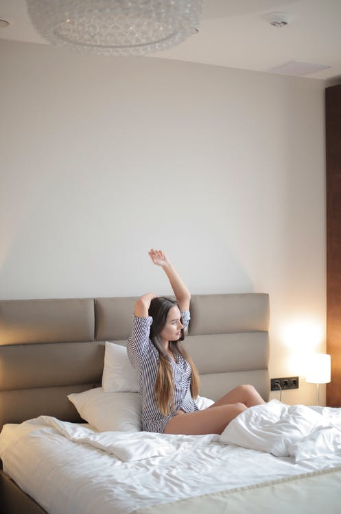 Positive young lady resting on comfortable bed in bedroom