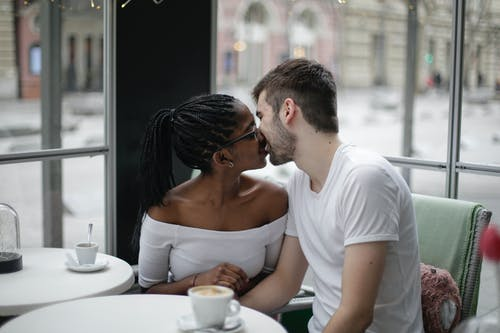 Happy young multiethnic couple kissing in modern cafe