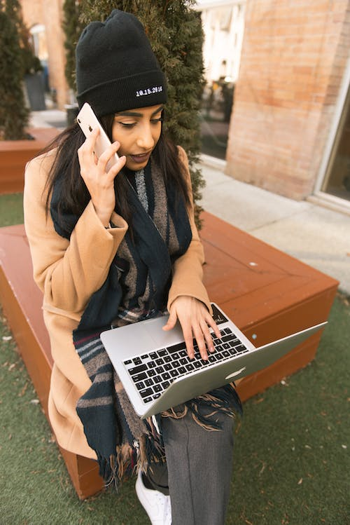 Woman Talking On The Phone While Using A Laptop
