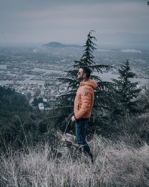 Man in Orange Jacket Standing on Grass Field