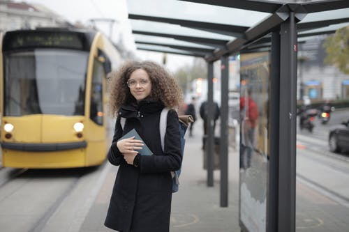 Girl in Black Coat Standing Near Yellow Bus