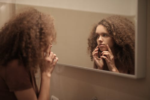 Serious young lady touching face while looking at mirror in bathroom