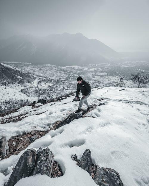 Man In Black Jacket Walking On Snow