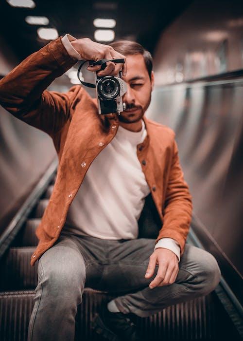 Foto profissional grátis de câmera, escada rolante, fotografando, homem