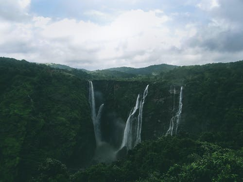 Landscape Photo of Waterfalls Between Green Trees